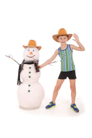 Cute boy holding a cola bottle near a snowman with scarf and hat on white background Stock Photo