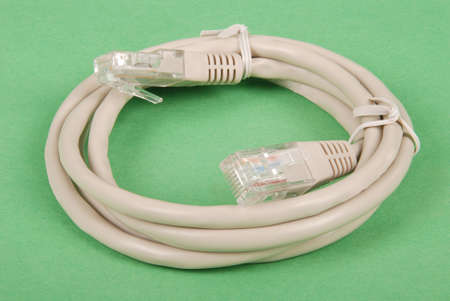 Patch cord grey network cable with molded RJ45 plug, isolated on a green background 스톡 콘텐츠