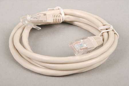 Patch cord grey network cable with molded RJ45 plug, isolated on a grey background