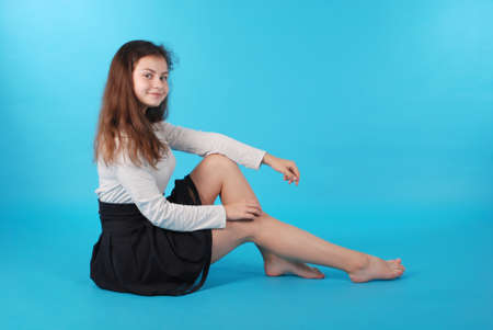 Young girl sitting on floor against blue background in studio.