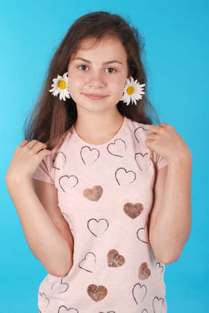 Beautiful young girl with chamomile earrings. Beauty girl with flowers on blue background. Standard-Bild