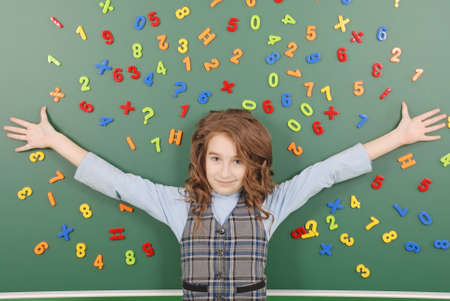 Girl stands in front of a green school board with magnets of numbers that depict her thoughts on green background 스톡 콘텐츠