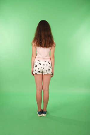 Rear view young girl with long hair looking at wall. Isolated on green background 免版税图像 - 112077585