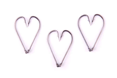 Strong fishing hook placed heart symbols on white background. A heart-shaped hook. 写真素材