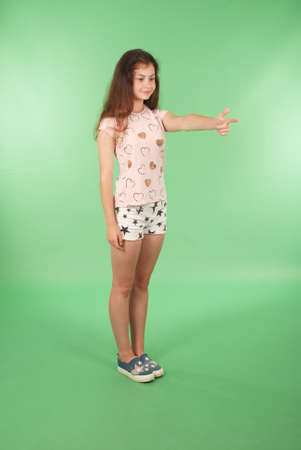 Side view young girl with raised hand looking at wall. Isolated on green background