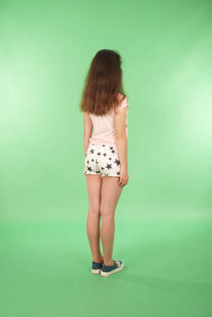 Side view young girl with long hair looking at wall. Isolated on green background Stock Photo
