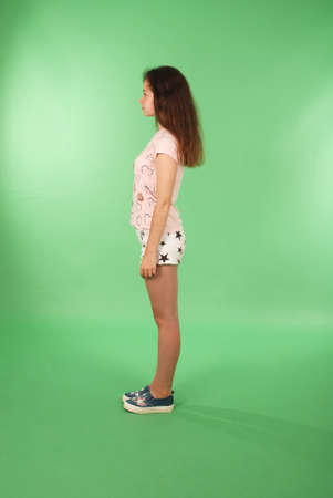 Side view young girl with long hair looking at wall. Isolated on green background Фото со стока