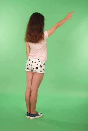 Side view young girl with raised hand looking at wall. Isolated on green background Reklamní fotografie - 112559856