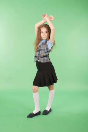 Beautiful young girl in school uniform isolated on green background 版權商用圖片