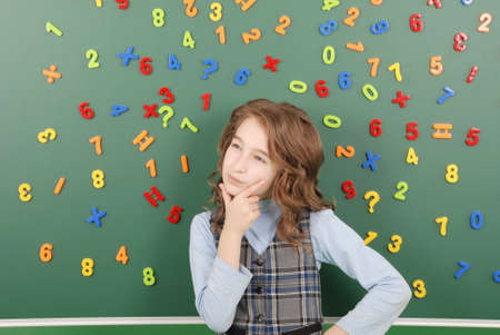 Girl stands in front of a green school board with magnets of numbers that depict her thoughts on green background Stock fotó