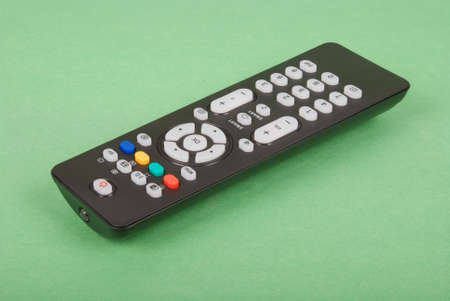 Black remote control for TV isolated on green background