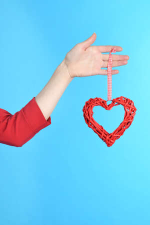 Woman hand holding symbol heart in hand isolated over blue background Standard-Bild