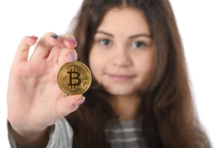 Pretty Girl holding new golden cryptocurrency bitcoin in hands on white background
