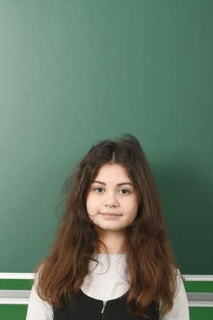 Smiling little schoolgirl on green school board Reklamní fotografie