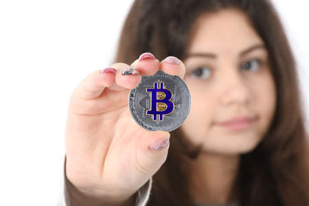 Pretty Girl holding in front of her new silver cryptocurrency bitcoin in hands on white background. Soft focus