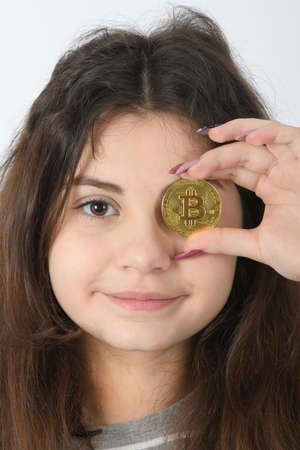 Pretty Girl holding in front of her new golden cryptocurrency bitcoin in hands on white background