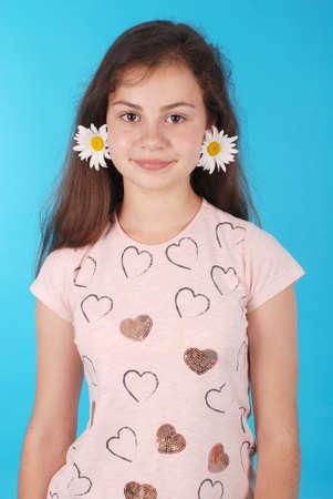 Hermosa joven con aretes de manzanilla. Chica de belleza con flores sobre fondo azul.