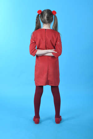 Full length studio photo girl wearing red dress standing on blue background. Back view.