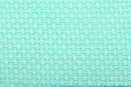 Texture of a polyethylene green shine gym mat. Yoga mat texture. Green polyethylene foam travel mat texture. High resolution photo.