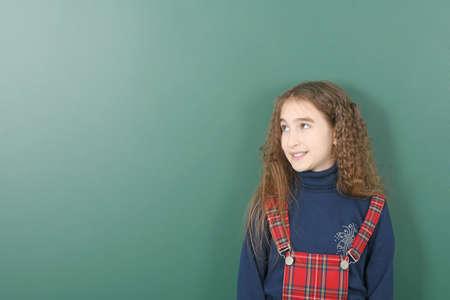 Schoolgirl near green school board. High resolution photo. Banco de Imagens