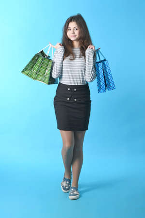Beautiful girl standing on a blue background with a package in the hands smiles a lovely smile