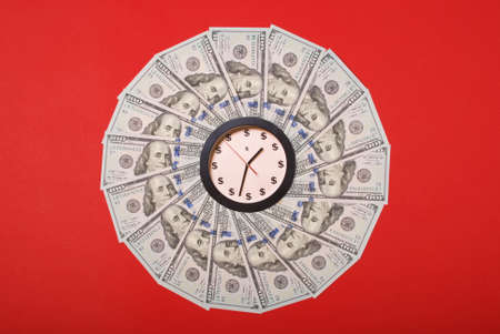 Concept of clock and dollar. Clock on mandala kaleidoscope from money. Abstract money background raster pattern repeat mandala circle. On red background.
