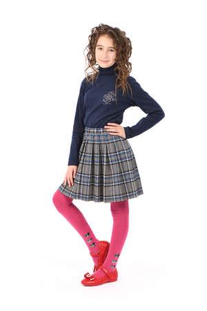 Portret van schattig lachend meisje kind schoolmeisje met krulhaar staande geïsoleerd op een witte achtergrond Stockfoto