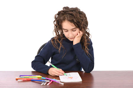 Young schoolgirl draws with markers while sitting at table, isolated over white. The concept of development of the child, the child's upbringing