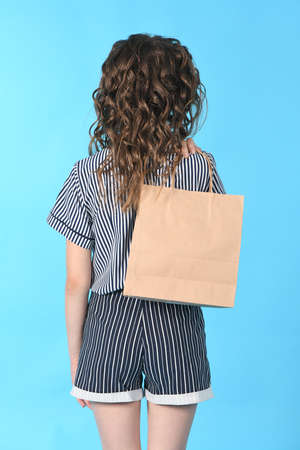 Child with a packet isolated on blue background. Holiday present, shopping. Kid happy shopping in mall. Happy girl with long curly hair. High resolution photo. Full depth of field. 스톡 콘텐츠