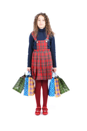 Child with a packaging checkered texture isolated on white background. Girl likes shopping on sale season. Holiday present, shopping. Autumn shopping concept. Happy girl with long curly hair. High resolution photo. Full depth of field. 스톡 콘텐츠