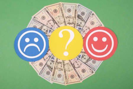 Question mark between smiley and sad smiley on mandala kaleidoscope from money. The concept of the level of earnings of men and women 版權商用圖片 - 131413302