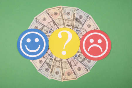 Question mark between smiley and sad smiley on mandala kaleidoscope from money. The concept of the level of earnings of men and women 版權商用圖片 - 131414315