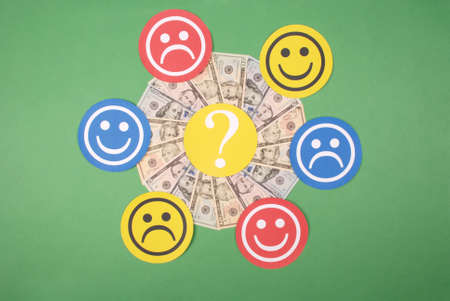 Question mark between smiley and sad smiley on mandala kaleidoscope from money. The concept of the level of earnings of men and women 版權商用圖片