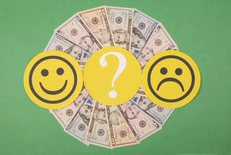 Question mark between smiley and sad smiley on mandala kaleidoscope from money. The concept of the level of earnings of men and women 版權商用圖片 - 131509499