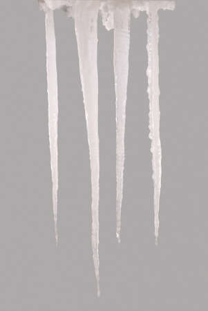 Icicles isolated on a grey background. Frozen water. Clipping path inside. Stock fotó