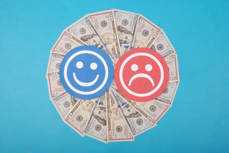 Smiley and sad smiley on kaleidoscope from money. Abstract money background raster pattern repeat circle. On blue background. High resolution photo.
