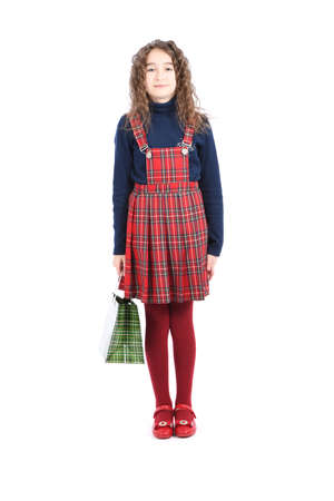 Child with a green packaging checkered texture isolated on white background. Girl likes shopping on sale season. Holiday present, shopping. Kid happy shopping in mall. Happy girl with long curly hair. High resolution photo. Full depth of field. 스톡 콘텐츠