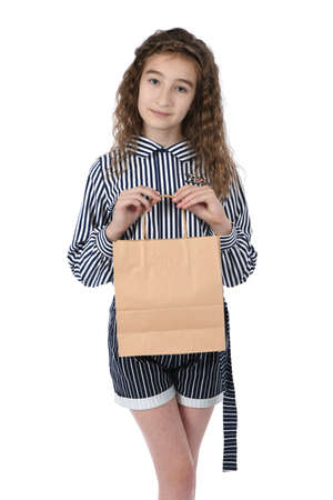 Child with a packet isolated on white background. Kid happy shopping in mall. Happy girl with long curly hair. High resolution photo. Full depth of field. Фото со стока