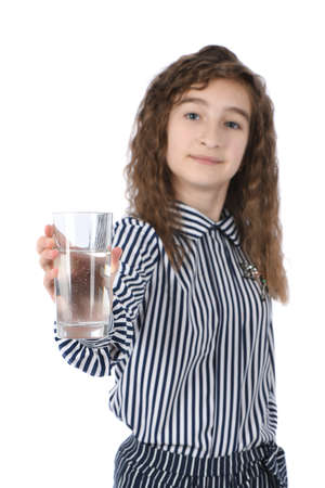 Beautiful young girl holding a glass of clean mineral water in her hand isolated on white. High resolution photo. Full depth of field.