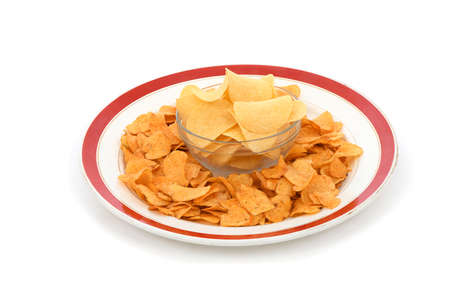Bowl is full of tasty crispy potato chips isolated on white background. High resolution photo. Full depth of field.