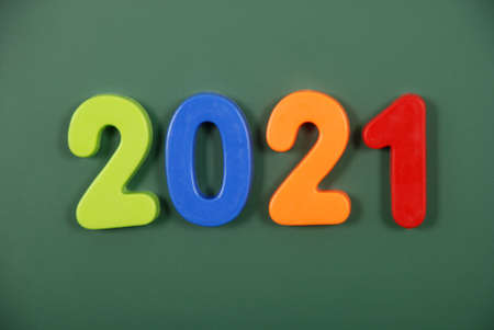 2021 year written in bright plastic magnetic letters stuck on a magnetic board