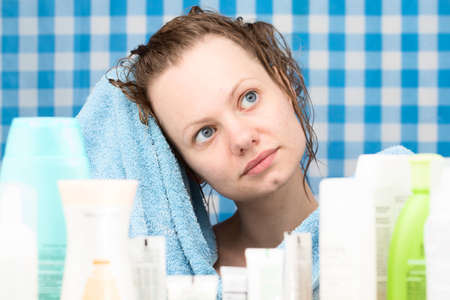 frontal portrait: Girl is drying her hairs surrounded by various cosmetics in bathroom. Skincare and beauty concept. Frontal portrait
