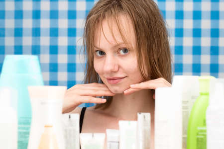 frontal portrait: Young girl with wet hairs is posing in the bathroom in front of cosmetic products at blue-and-white checkered curtains background. Skincare and beauty concept. Frontal portrait Stock Photo