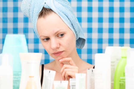 shower stall: Girl with towel on her head is looking at cosmetic products in bathroom. Skincare and beauty concept. Frontal portrait