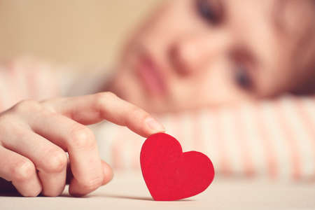 dejection: Sad girl is holding heart symbol by her finger and looking at it. Love and relationships concept Stock Photo
