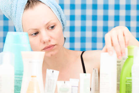 shower stall: Girl with towel on her head is choosing cosmetics at blue curtain background in bathroom. Skin care and beauty concept