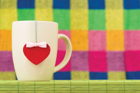 valentine day cup of coffee: Heart symbol with a bow and a cup on a bamboo napkin on a color checkered background Stock Photo