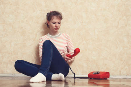 liaison: Sad young white-skinned girl is sitting on parquet floor beside the wall and calling by red phone Stock Photo