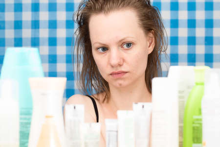 frontal portrait: Young white-skinned girl with wet hair without makeup is looking at cosmetic products in bathroom. Skincare and beauty concept. Frontal portrait