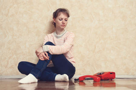 liaison: Sad young white-skinned girl is sitting on parquet floor beside the wall near to red phone